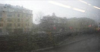 Likainen bussin ikkuna, jonka läpi näkyy sumeasti kaupunkimaisemaa.