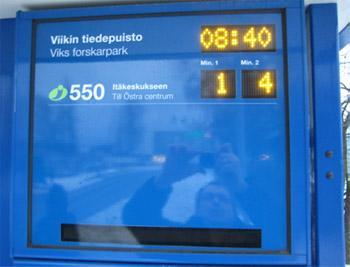 Pysäkillä oleva näyttö, jossa näkee linja-auton numeron ja montako minuuttia on kunnes seuraavat kaksi bussia tulevat. Näytössä on myös kello.