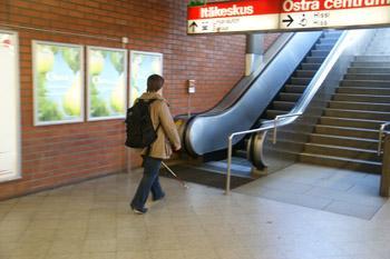 Nainen on astumassa ylöspäin meneviin liukuportaisiin Itäkeskuksen metroasemalla.