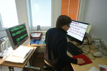 Nainen istuu kirjoituspöydän ääressä ja katsoo tietokoneen ruutua, jossa on suurennusohjelma. Vasemmalla on lukutelevisio.