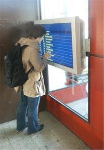 Nainen seisoo metroasemalla olevan aikataulunäytön edessä.