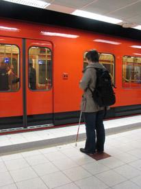 Nainen seisoo metrolaiturilla. Hänen edessään on metrojuna, jolla on ovet kiinni.