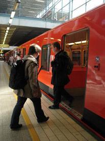 Nainen on astumassa sisään metrovaunuun. Samalla metrosta tulee ulos mieshenkilö.