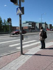 Nainen seisoo odottamassa suojatien kohdalla. Jalankulkioiden valot ovat punaisella.