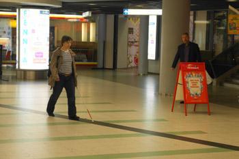 Nainen seuraa tummanväristä ohjaavaa raitaa Helsingin yliopiston metroasemalla.