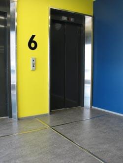 Ohjaava metallilista lattiassa hissin oven edustalla.