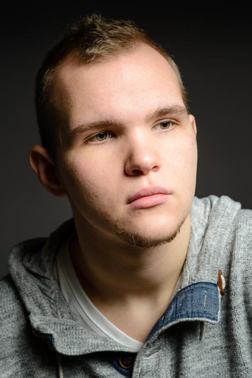 Muotokuva 22-vuotiaasta nuoresta miehestä. Hänellä onb vaaleanruskeat lyhyet hiukset ja vihertävänruskeat silmät. Hänellä on pieni leukaparta ja tummat kulmakarvat. Ilme on vakava. Yllään hänellä on harmaa neulehuppari.
