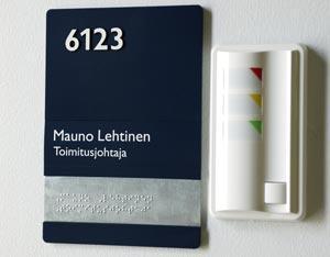 Huoneopaste, jossa lukee huoneen numero ja henkilön nimi. Opasteessa on myös samat tiedot pistekirjoituksella.
