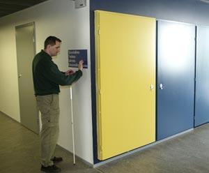 Käytävien risteyskohdassa on oikealla kirkkaankeltainen ovi ja vasemmalla mieshenkilö lukee pistekirjoitusta opastekyltissä.