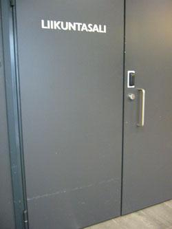 Harmaa ovi, jossa lukee valkoisella liikuntasali.