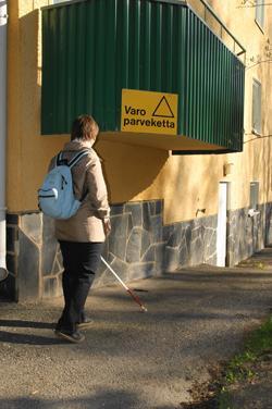 Nainen kulkee jalkakäytävällä kohti hyvin matalalla olevaa parveketta. Parvekkeessa on keltainen kyltti, jossa lukee Varo parveketta.
