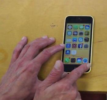 Älypuhelin kosketusnäytöllä, käyttäjän sormet ihan kosketusnäytön alalaidassa.
