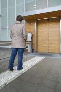 Nainen seuraa ohjaavaa laattaa, joka johtaa Iiris-keskuksen pääsisäänkäynnille.