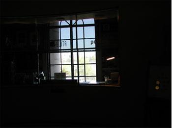 Taustalla on ikkuna, josta tulee valoa sisään tummaan huoneeseen.