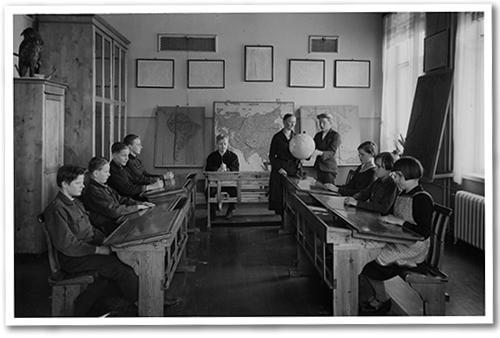 Mustavalkoinen kuva vanhasta koululuokasta. Keskellä on opettaja ja oppilaiden pulpetit ovat huoneen reunoilla.