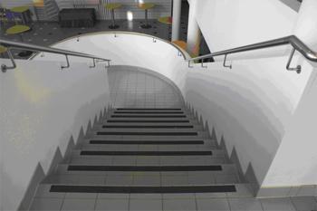 Alaspäin menevät portaat, joiden askelmissa on kontrastiraidat.