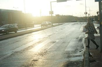 Märkä asfaltti, josta valo peilautuu. Etuosassa on suojatie, jonka yli nainen on juuri menemässä.