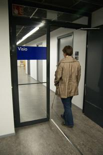 Nainen kulkee oviaukosta sisään. Vasemmalla on lasiseinä, jossa on kyltti Visio.