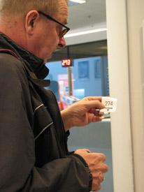 Mieshenkilö pitää kädessään vuoronumerolappua, jossa on numero 274.