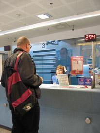 Mieshenkilö seisoo palvelutiskin edessä ja keskustelee tiskin toisella puolella olevan naisvirkailijan kanssa.