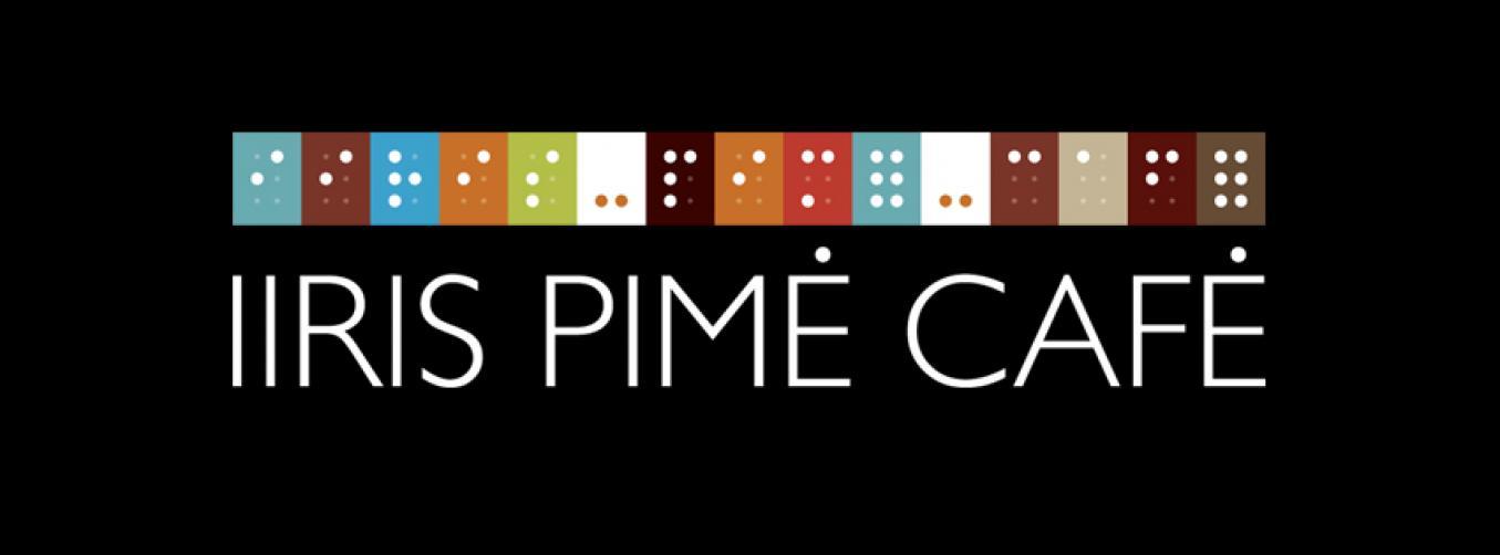 Mustalla pohjalla lukee valkoisella Iiris Pimé Café. Sama teksti on myös pistekirjoituksella.