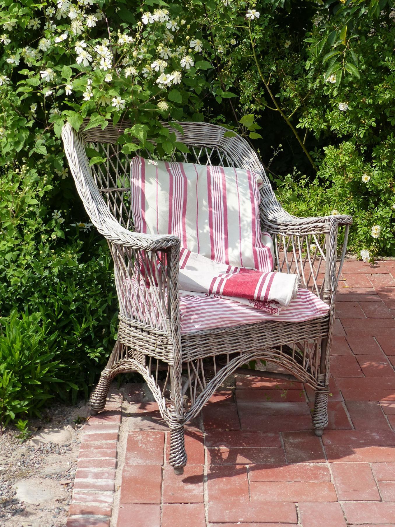Korituoli pensaan vieressä ja tuolilla on punavalkoraidallinen kangas
