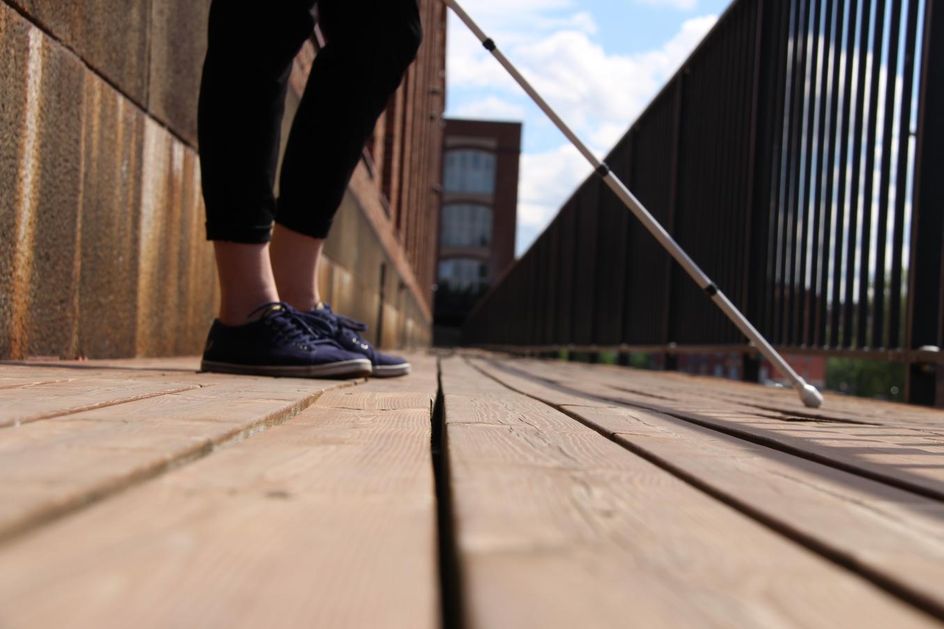 Nainen seisoo sivuttain puisella sillalla, kuva pohkeesta alaspäin. Kädessä nainen pitää valkoista keppiä ja pitää sitä edessään. On kesäpäivä.