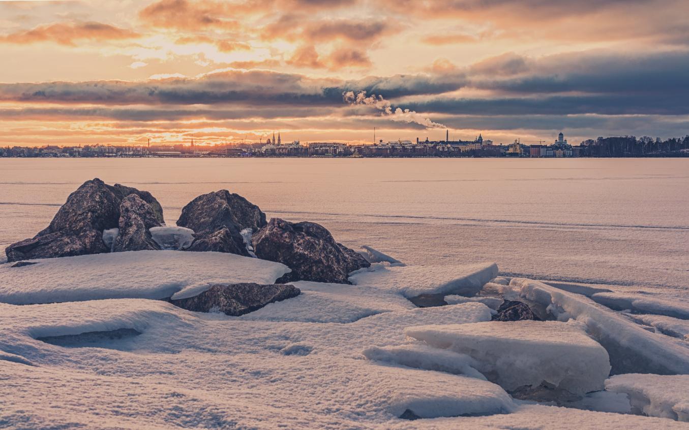 Luminen ja hämärä Helsingin rantaviiva talvella, meri jäässä ja lumen peitossa.
