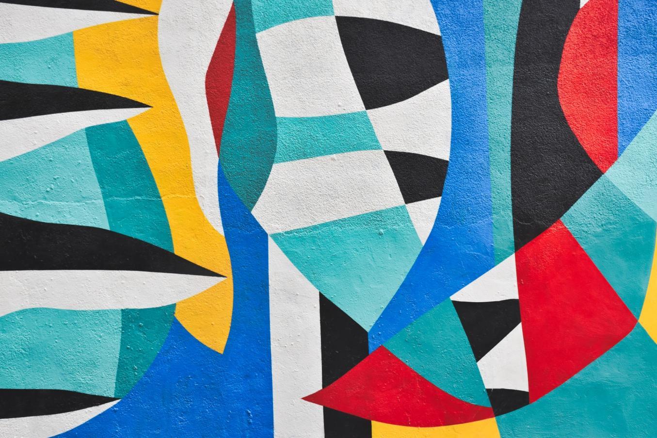 Erivärisiä abstrakteja kuvioita seinälle maalattuna.