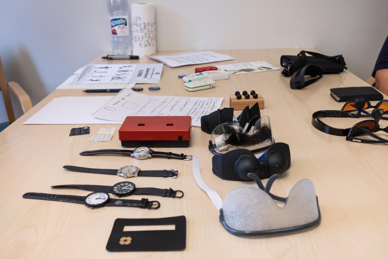 Pöydällä erilaisia rannekelloja, apuvälinelaseja ja muita tarvikkeita kokemuskoulutustilannetta varten.