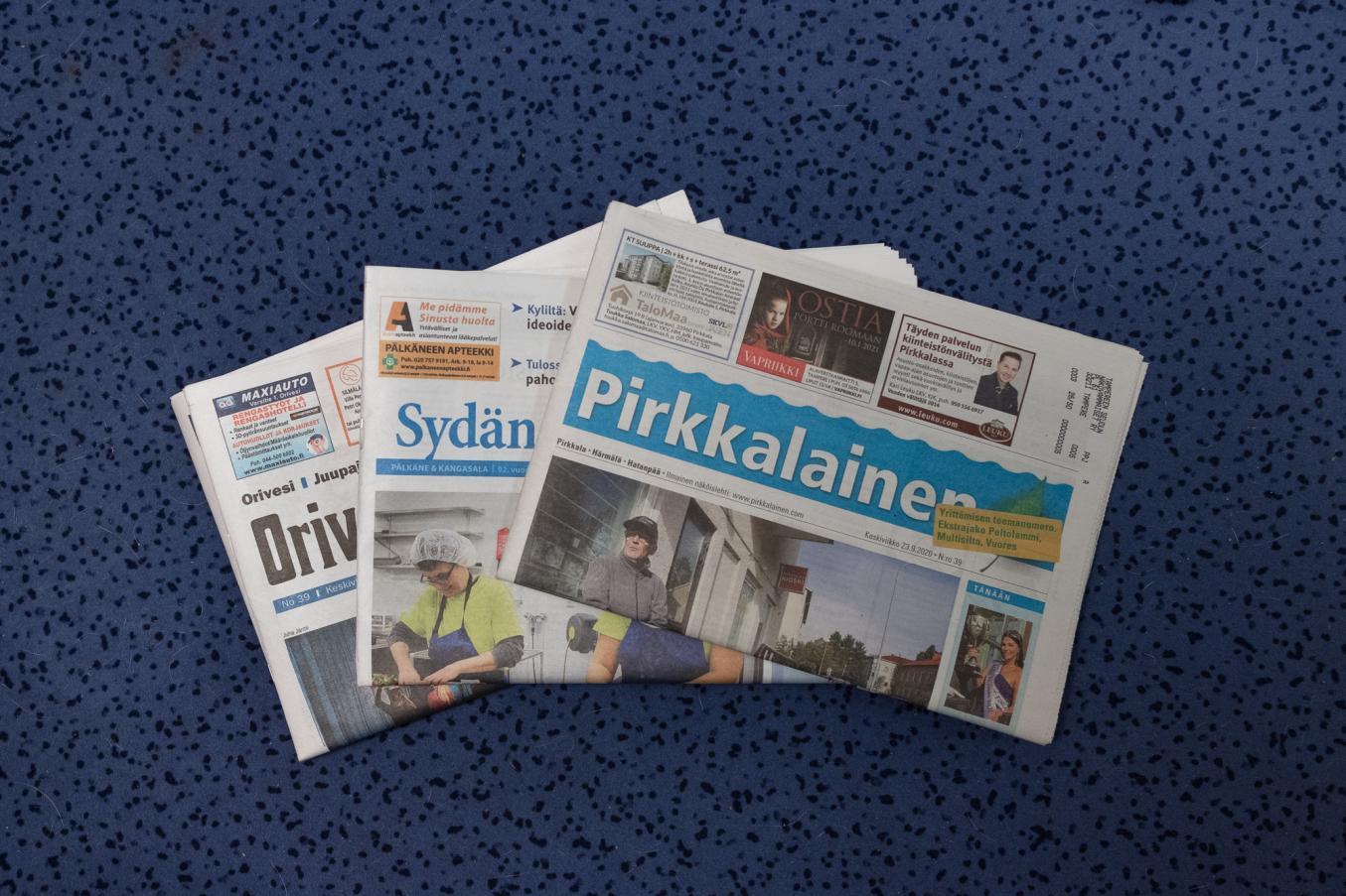 Sinisellä taustalla kolme paikallislehteä lomittain päällekkäin vinosti pinottuna.