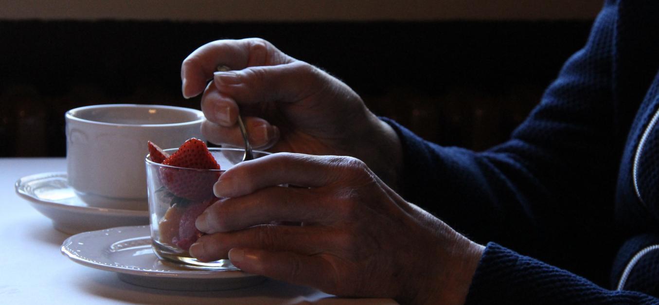Hämärässä pöydällä kahvikuppi ja mansikoita lasikipossa. Nainen pitää kättään mansikkakipon ympärillä ja on ottamassa lusikalla mansikoita lasista.