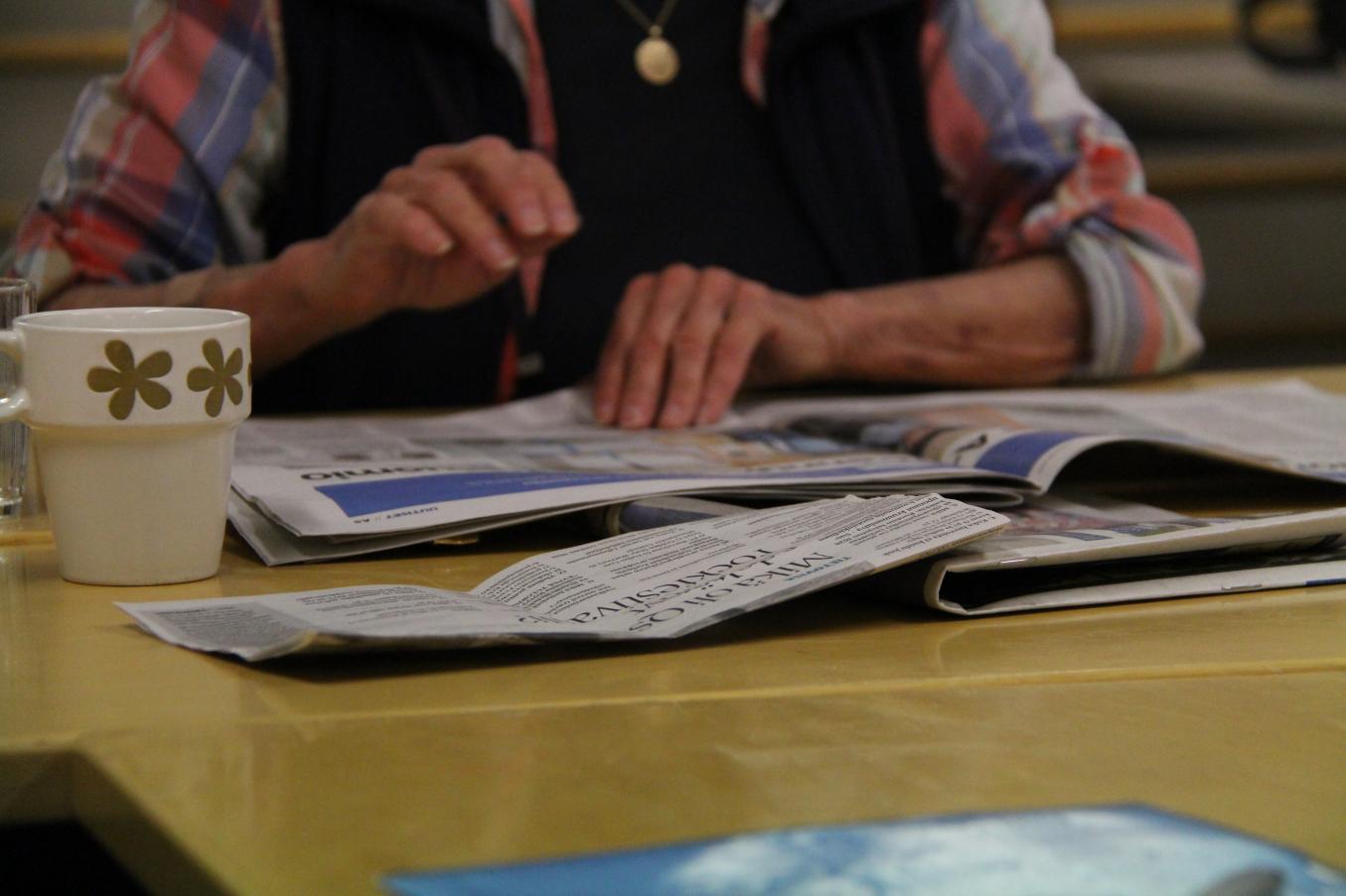 Nainen lukee sanomalehtiä pöydän ääressä, pöydällä lisäksi useita muita lehtiä ja kahvikuppi.
