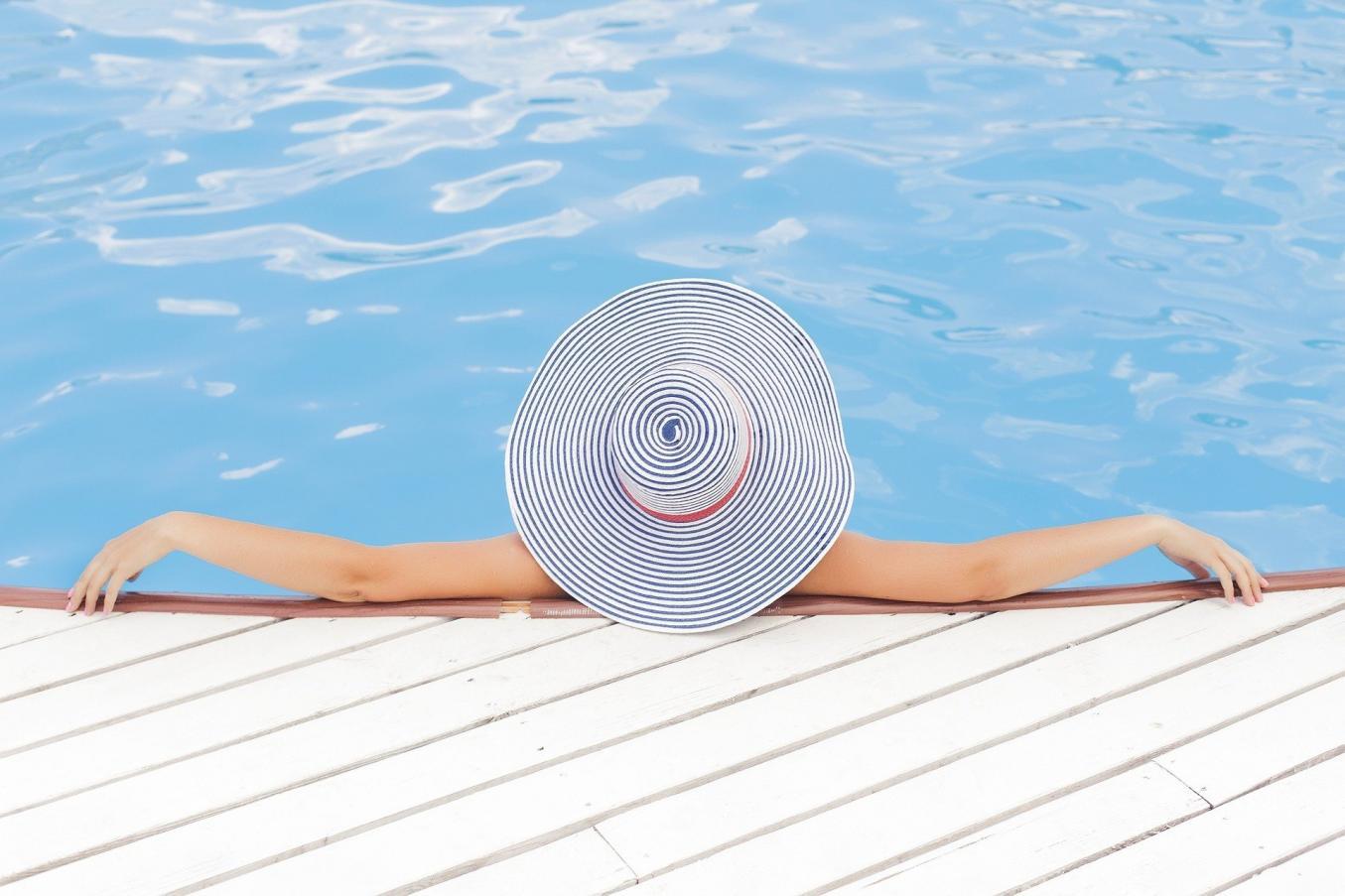 Uima-altaassa nainen, josta näkyy vain hattu ja kädet.