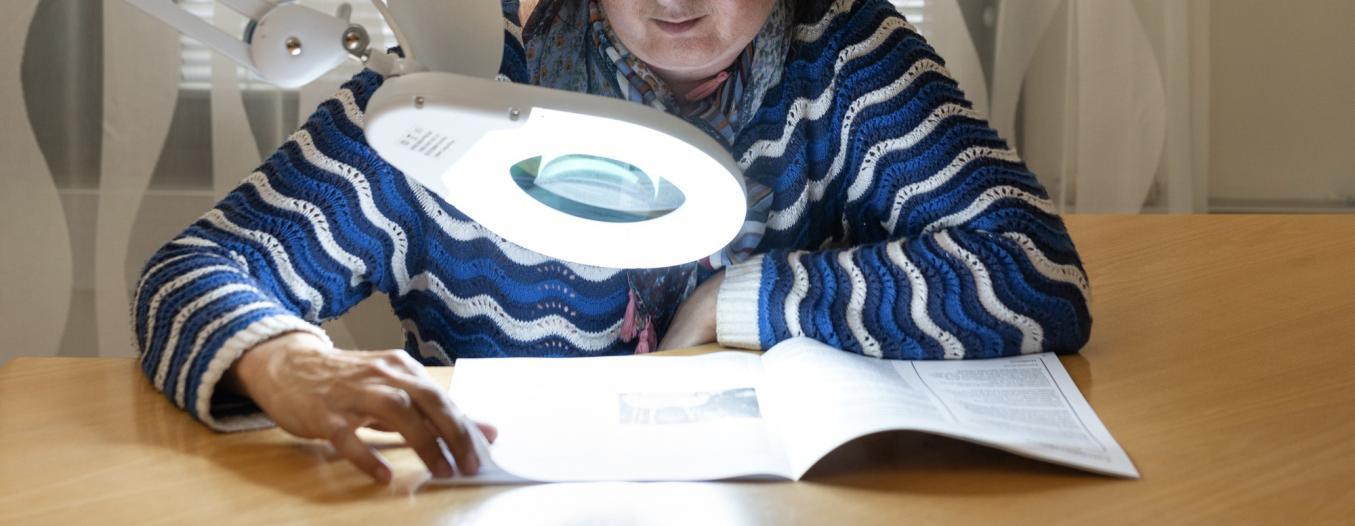 Nainen lukemassa lehteä pöytään kiinnitettävän suurennuslaitteen avulla.