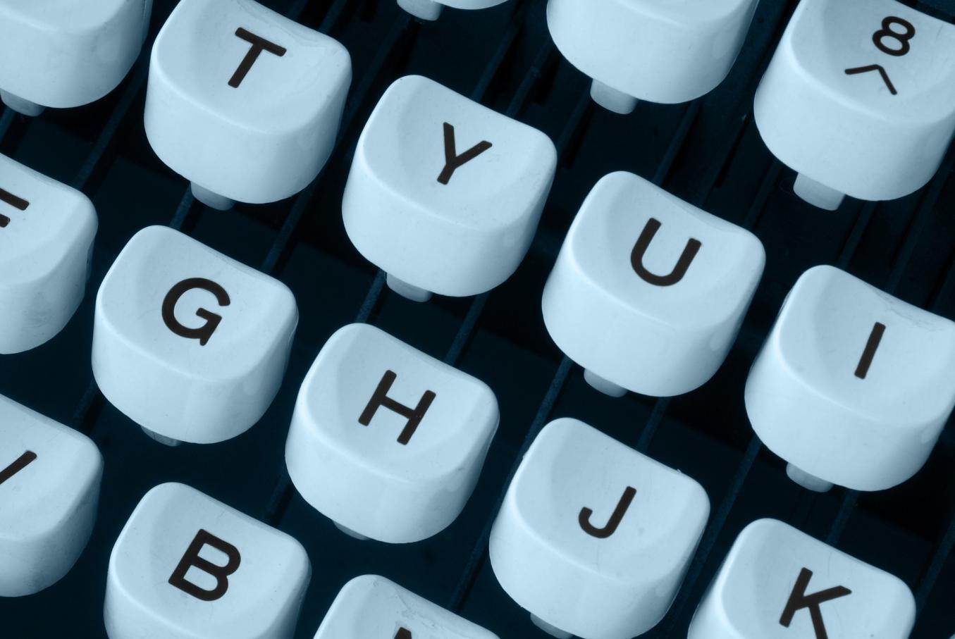 Kuvassa kirjoituskoneen valkoiset näppäimet mustalla tekstillä