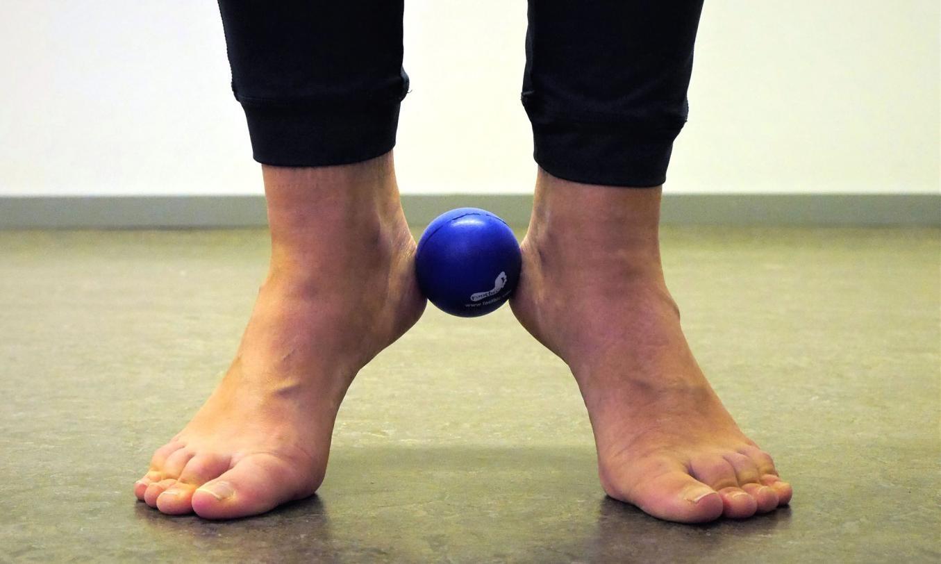 Ihminen tekee seisaallaan varvistusharjoitetta niin, että footbic-pallo on tuettu kantapäillä jalkojen väliin.