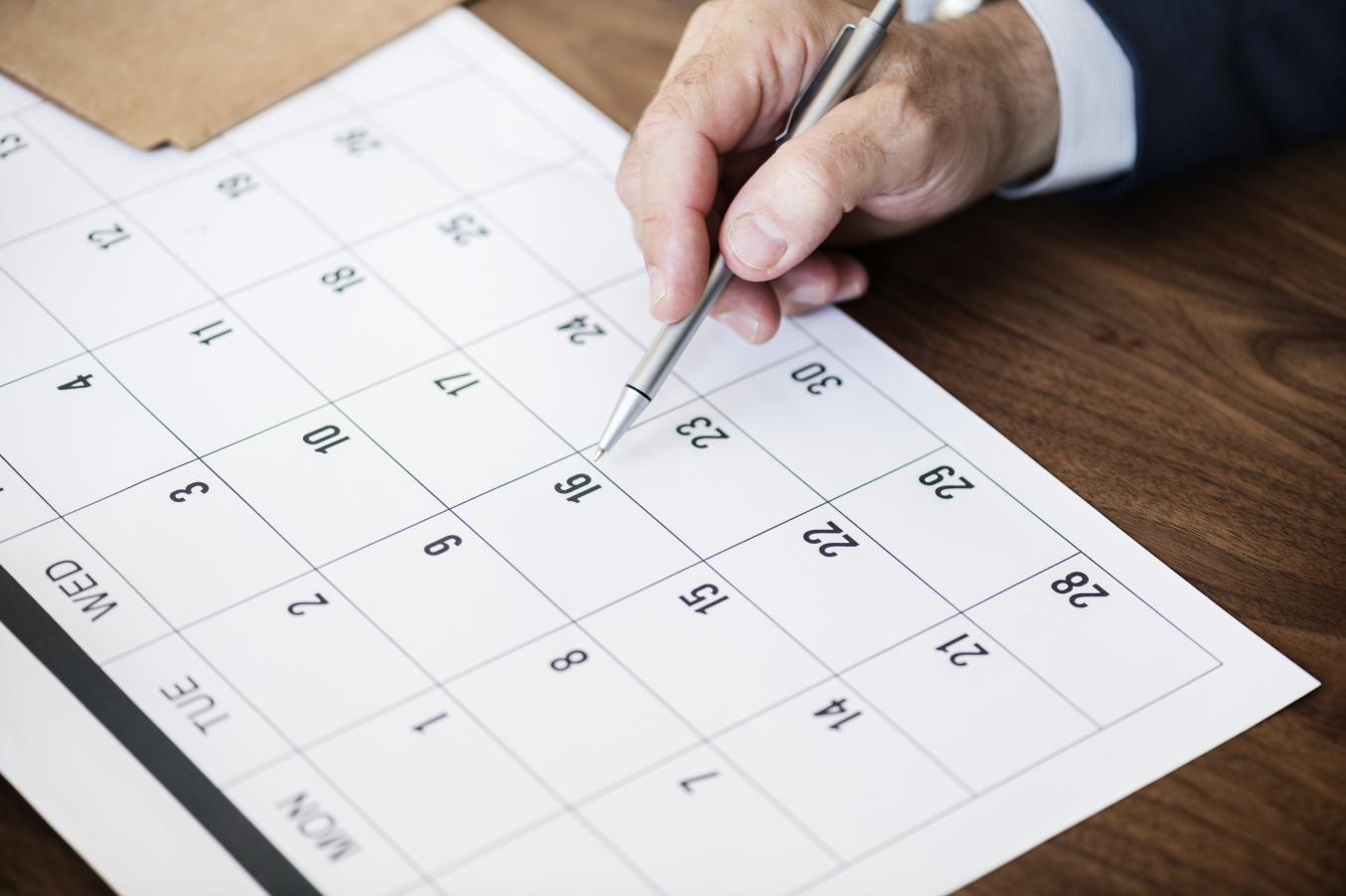 Henkilö tutkii pöydälle levitettyä kalenteria.