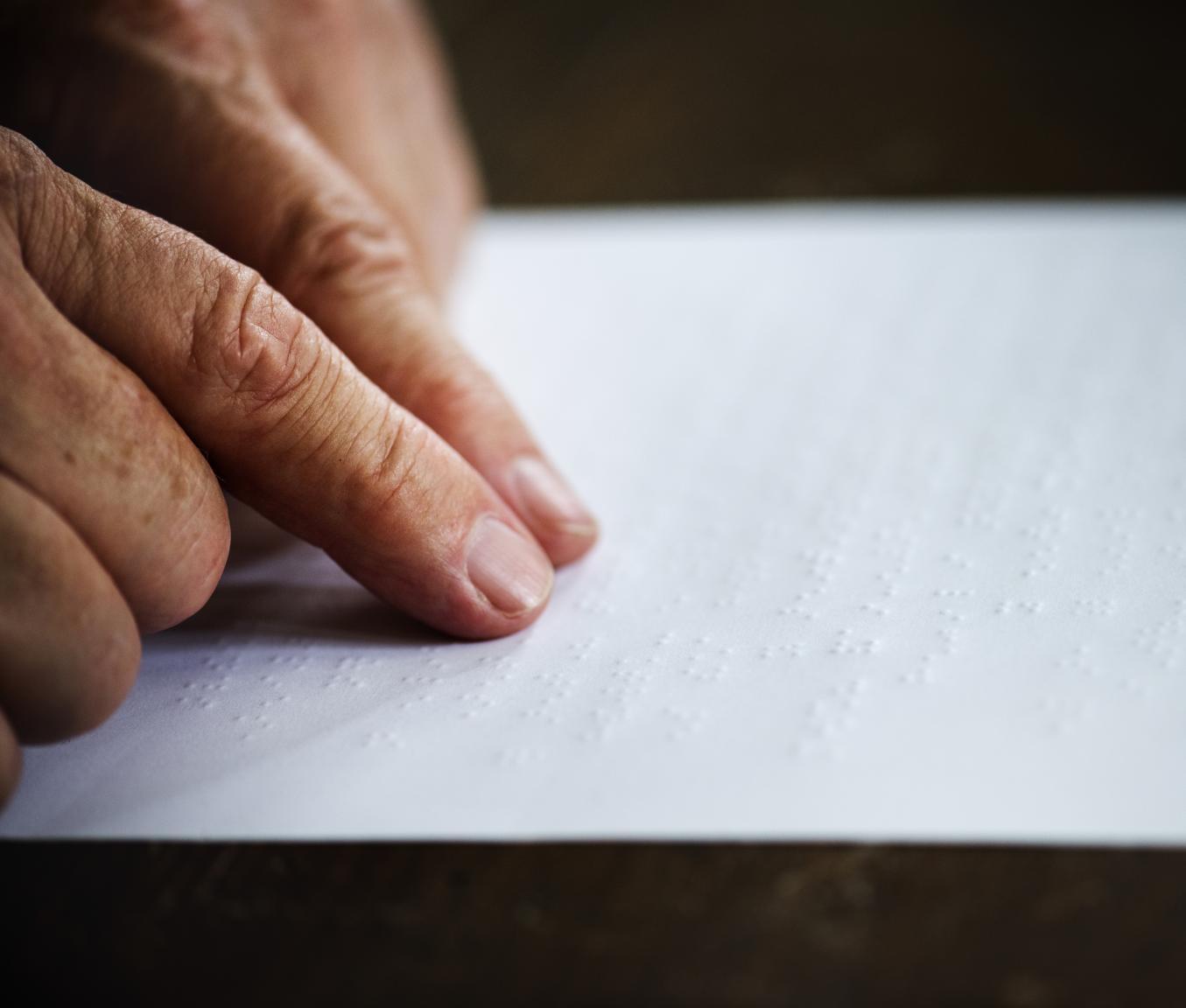 Henkilö lukee paperilta pistekirjoitusta, kamera on kohdistunut käsiin ja paperiin.