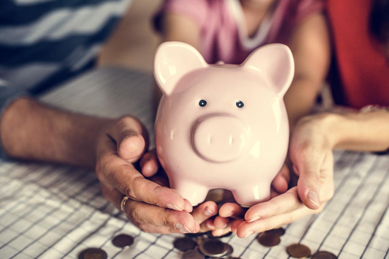 Vaaleanpunainen säästöpossu, jota pitelevät kolmen ihmisen kädet.