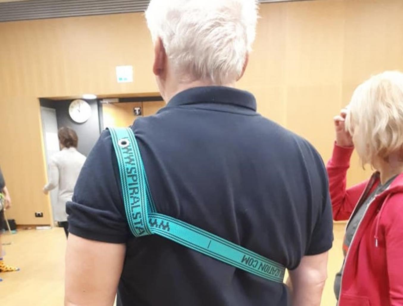 """Mies seisoo selin kameraan, ja hänen ylävartalonsa ympärille on kiedottu kuminauha, jossa lukee """"spiraalistabilaatio""""."""