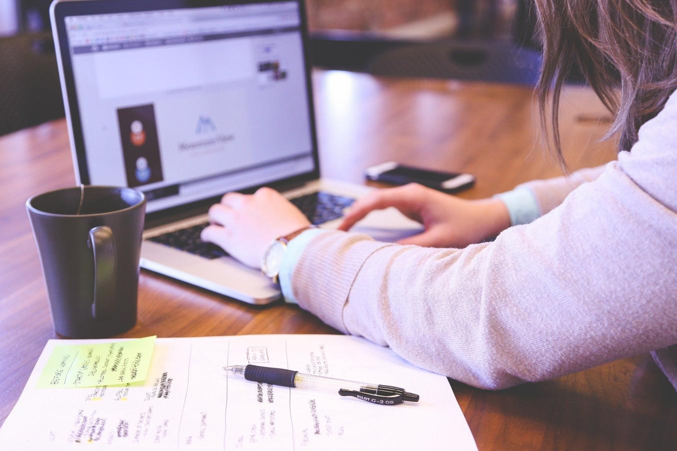 Nainen kirjoittaa tietokoneella. Pöydällä kahvikuppi, asiakirja, kynä ja puhelin.