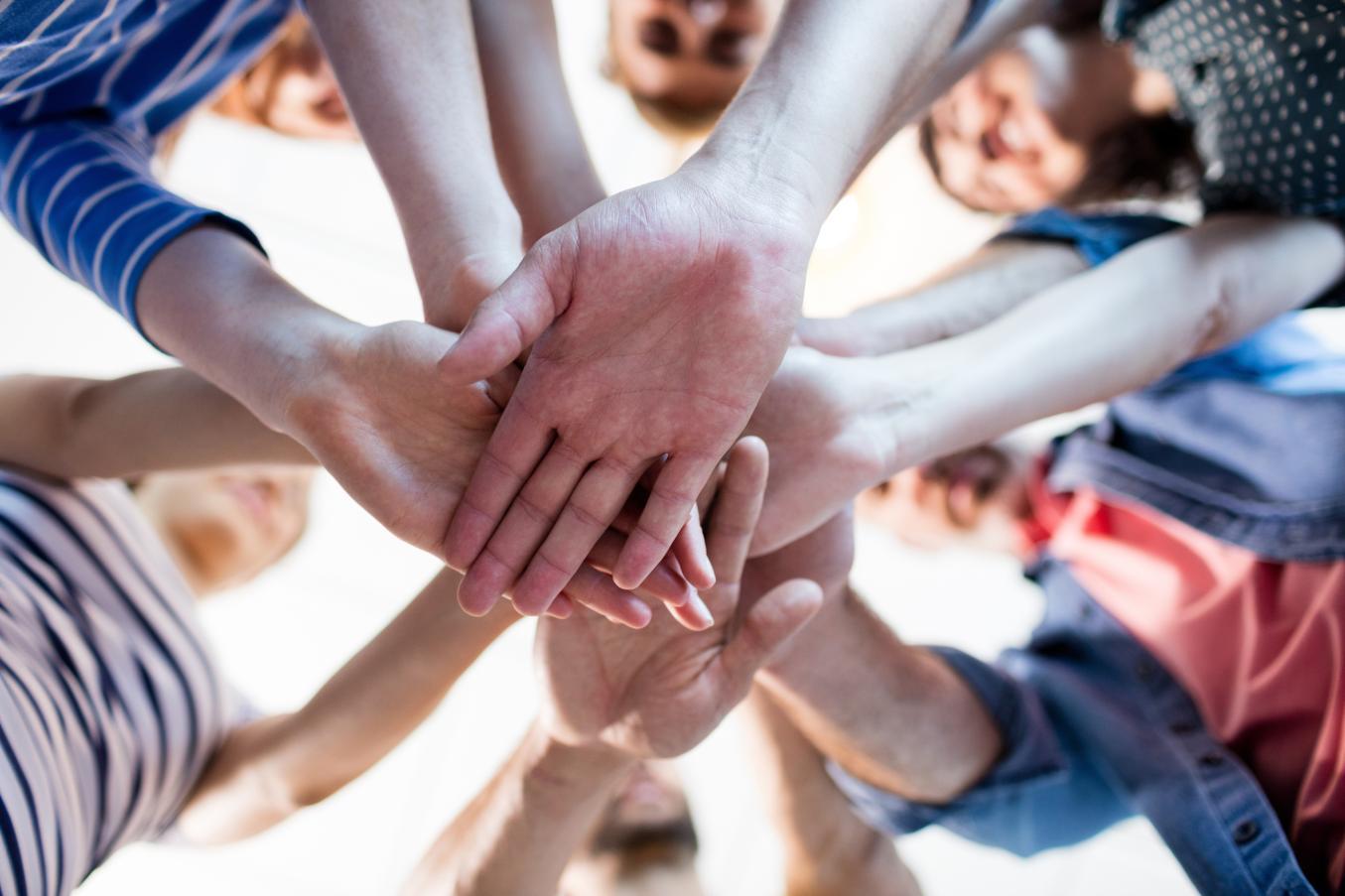 Useat ihmiset yhdistävät kätensä päällekkäin keskelle kuvaa yhtenäisyyden merkiksi.