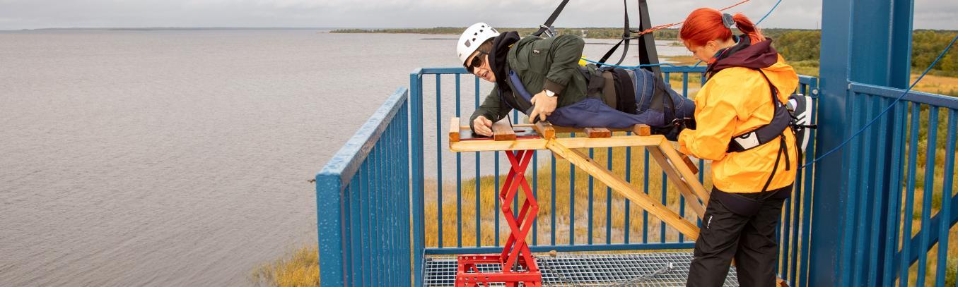 Retkeläinen valmistautumassa vaijeriliukuun ja järjestäjä laittaa turvallisuusremmejä paikoilleen