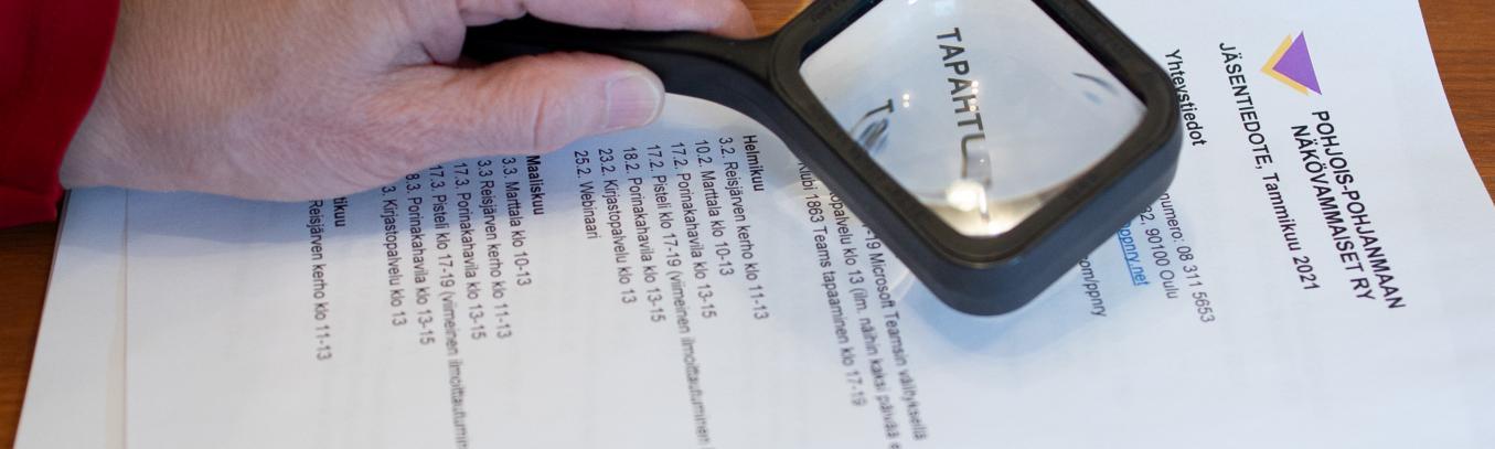 Kuvassa henkilöllä on kädessä suurennuslasi ja sen alla paperinen jäsentiedote