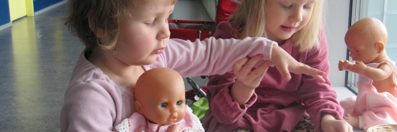 Kaksi tyttöä leikkivät kahvikutsuja. Molemmilla on nuket ja oikealla oleva tyttö ohjaa kädellään vasemmalla puolella olevaa tyttöä löytämään kahvikupin.