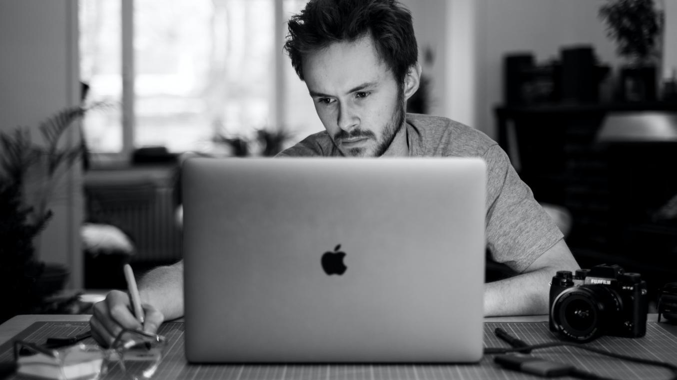 Mies istuu Apple-tietokoneensa ääressä ja tuijottaa ruutua ja kirjoittaa samalla kynällään jotain. Vieressä kamera. Mustavalkoinen.