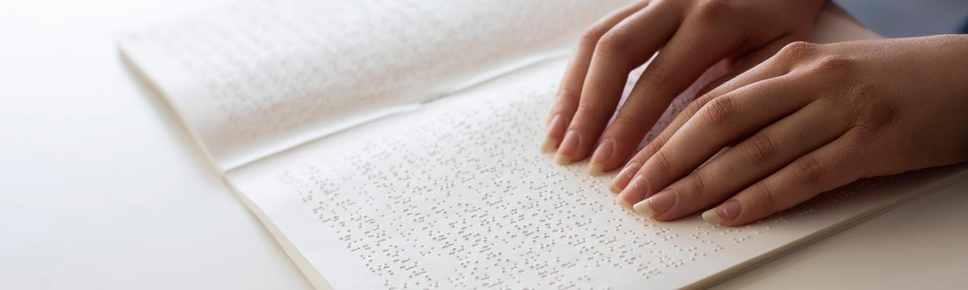 Kädet lukemassa pistekirjoitusta.