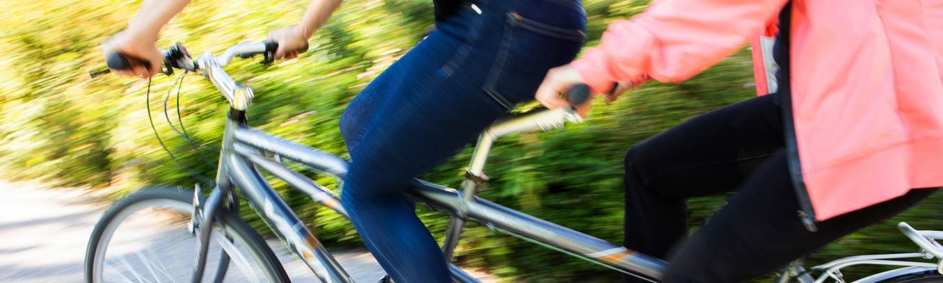 Kaksi henkilöä ajaa tandempyörällä. Kuvattu keskivartalosta alaspäin.