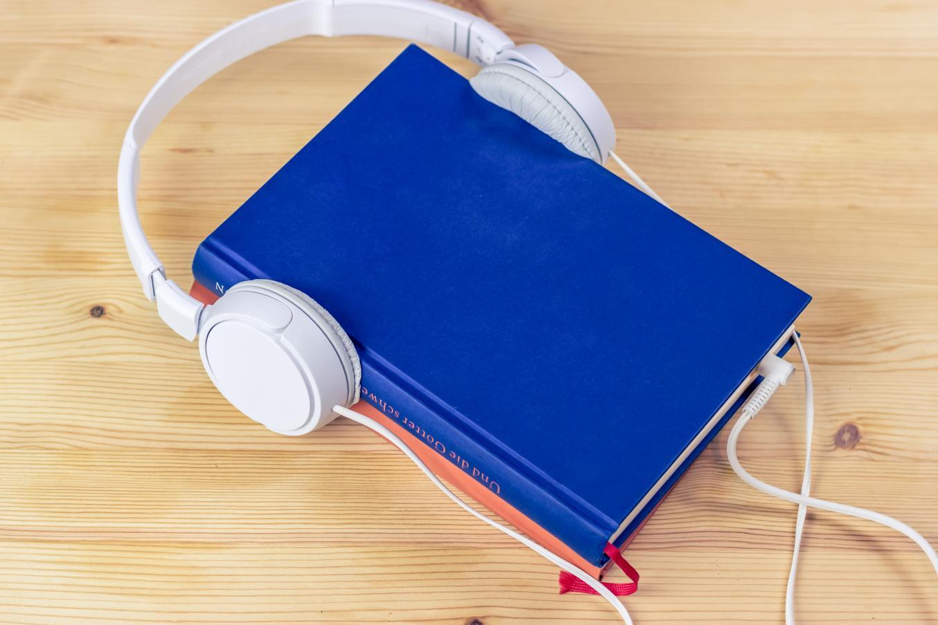 Pöydällä lepää sininen kirja, jonka ympärille on aseteltu valkoiset kuulokkeet.
